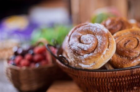 Basket with cinnamon rolls and berries on background selective focus