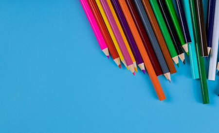 Color pencils on light blue background, school supplies