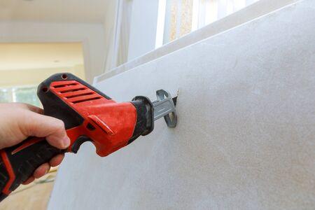 Plasterboard cutting of drywall hand with grunge dirty saw 版權商用圖片