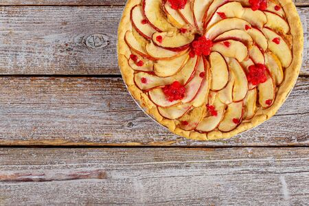 Homemade apple pie with sliced apples on the top on wooden background