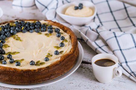 Blaubeer-Käsekuchen, Tasse Kaffee und Pudding auf weißem Tisch