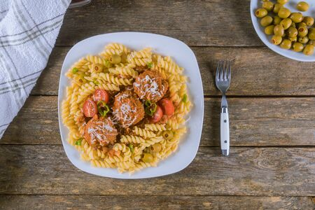 Meatballs with rotini pasta and sauce in white plate. Top view