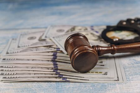 Judge gavel of metal police handcuffs and US dollar banknotes corruption, dirty money financial crime
