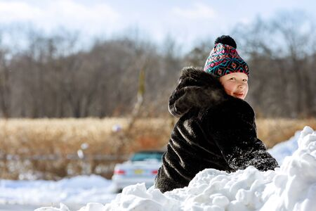 Happy child playing in snow outside on cold winter day.