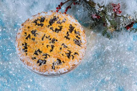 Christmas blueberry pie with snowflakes on frosty snow.