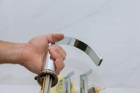 Plumber installing new mixer tap hands worker close up repair in bathroom at home plumbing repair service