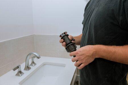 Repair in bathroom at home plumber installing new drain hands worker close up
