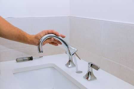 Repair service, assemble and install new faucet lies on the ceramic sink