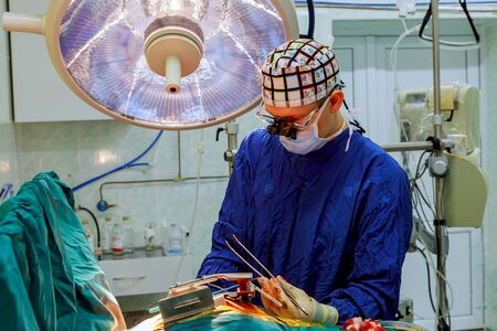 Surgeons performing open heart surgery in young surgery team in the operating room