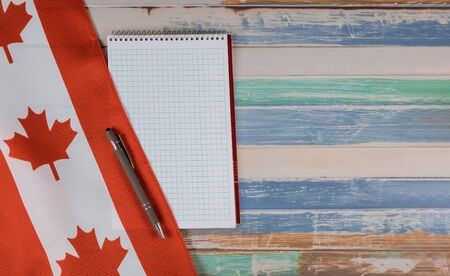 Holiday Happy Victoria Day Canadian flags notepad with pen of Canada independence day rustic background