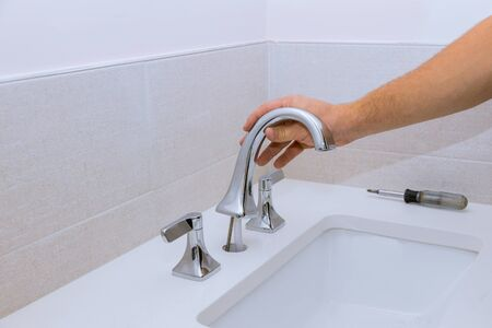Plumber repair service, assemble and installing water faucet in the bathroom Stockfoto