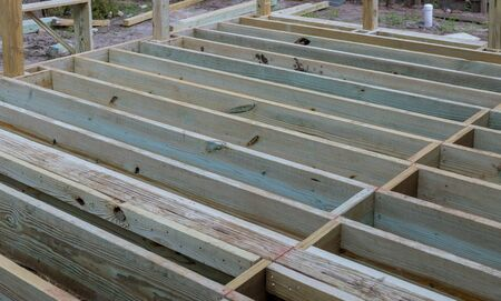 A new wooden, timber deck being constructed. it is on the decking. New deck patio