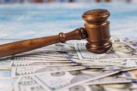 Court wooden gavel and money on blue background.