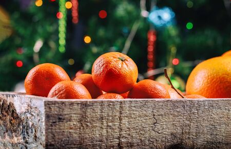 Wooden box of tangerines and oranges with Christmas tree. Reklamní fotografie