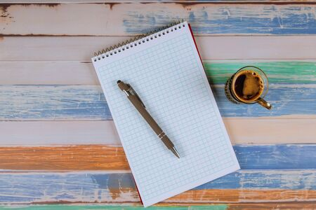 Notebook, pen and cup of coffee on colorful table.