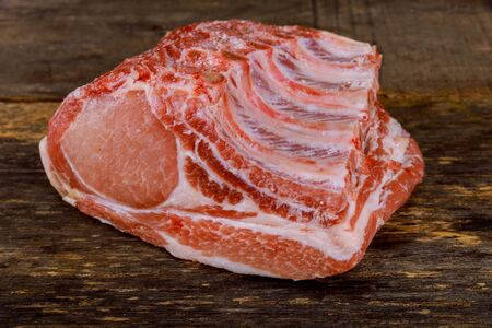 Raw pork meat on ribs isolated on wooden background. Reklamní fotografie