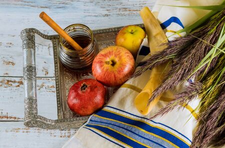 Rosh hashanah jewesh holiday concept shofar, honey, apple and pomegranate over wooden table.