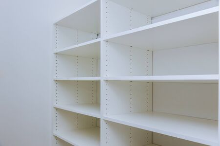 Interior of white plastic cabinet or clothing with many empty shelves with installation new home Stockfoto