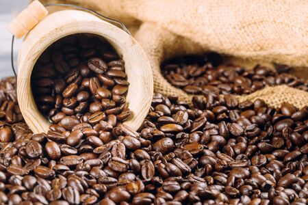 Coffee beans in a decorative bucket on a roasted coffee beans background