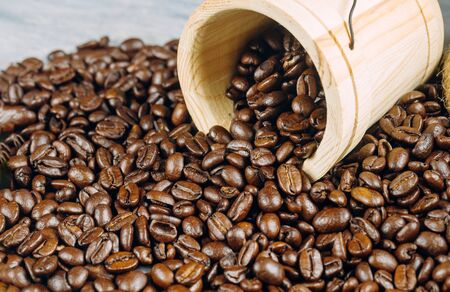 Coffee beans in small wooden bucket with roasted coffee beans background