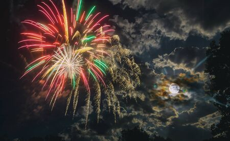 Night fireworks different colors glittering sparkle fireworks on a Nightly sky with large moon and eerie white clouds