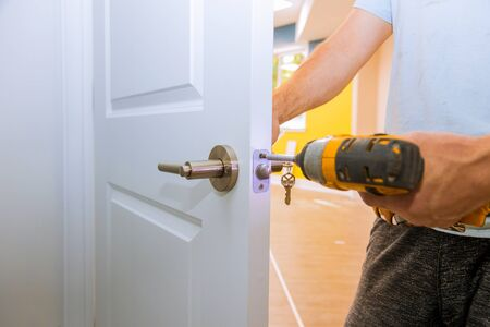 Carpenter at lock installation with out the door knobs wood door