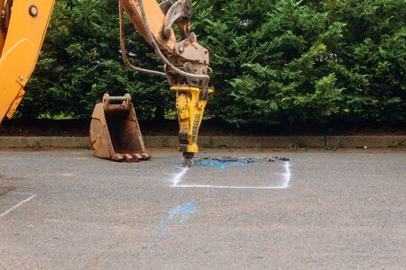Construction worker repairing road with operating digger Jackhammer