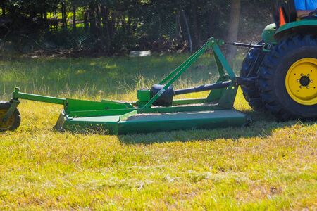 Mowing or cutting the long grass with a lawn mower in the summer sun