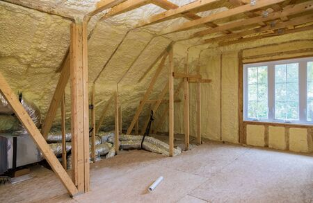 Foam plastic insulation installed in the sloping attic of a new frame house.