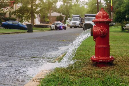 Water flowing from in open red fire hydrant is wet from the spray. Banco de Imagens