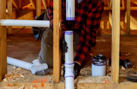 Plumber installing primer and glue PVC pipe at construction new home Reklamní fotografie