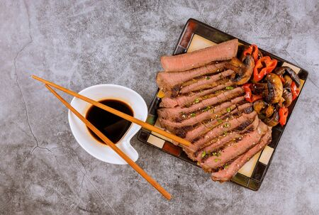 Korean sweet fried beef and mushrooms, toasted sesame seeds, soy sauce, in black plate with chopsticks