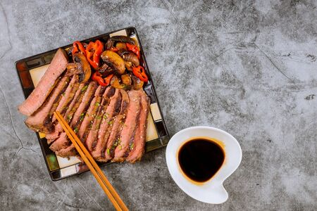Beef Korean grilled beef made thinly sirloin of steak fried, red bell peppers and mushrooms on plate with chopsticks