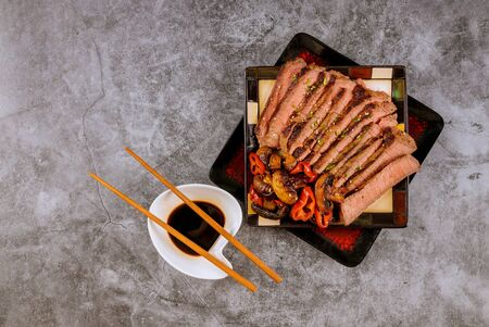 Chinese style sliced roast beef steak fried mushrooms sesame seeds, soy sauce with chopsticks