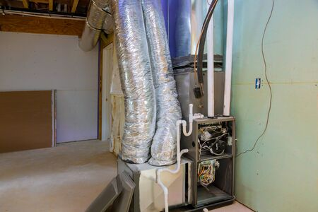 New home construction with installation of heating system in basement of house under remodeling Imagens