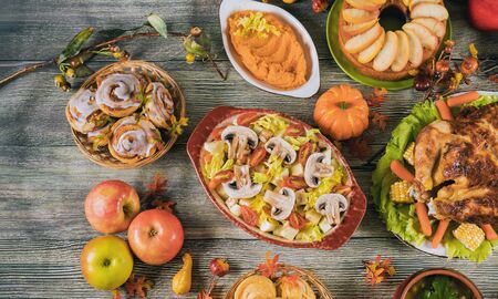 Thanksgiving dinner served with turkey, apples, sweet potato, decorated with autumn leaves and pumpkin.