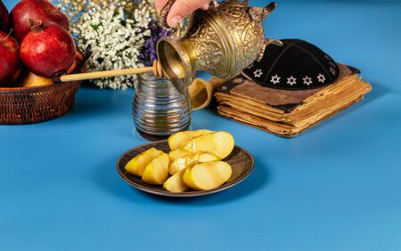 A female hand takes a with honey for the apple slice and pomegranate holiday of Rosh Ha Shana Jewish prays at the praying book 版權商用圖片