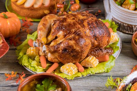 Thanksgiving dinner with roasted turkey garnished with corn and pumpkin. Stockfoto