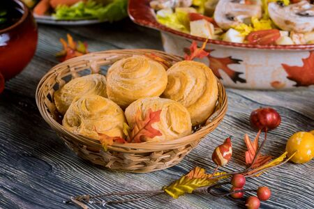 Swirl buns on wicker basket with autumn decoration on table. Reklamní fotografie