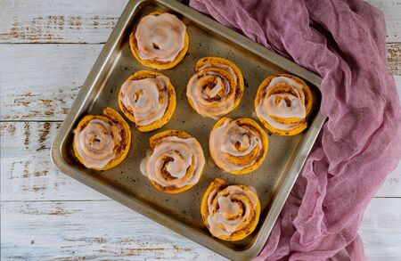 Homemade cinnamon rolls in baking pan on white wooden table.