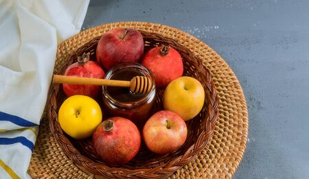 Pouring honey on apple and pomegranate with honey symbols of Jewish New Year Rosh Hashanah.