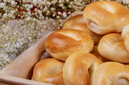 Fresh homemade bagels in wooden tray with flowers.