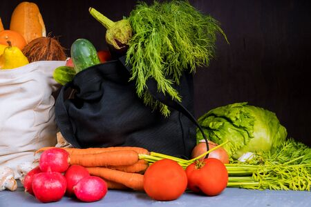 Shopping, groceries, bags full of vegetables and fruits on black background.