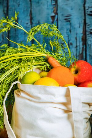 Full white, reusable grocery bag with fruits and vegetables.