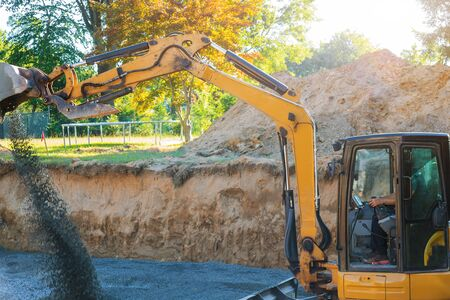 Industrial construction site excavator moving gravel and rocks for foundation under construction home