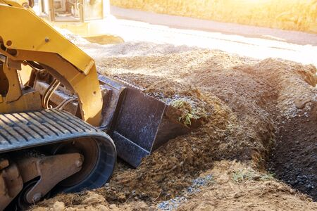 Mini bulldozer travaillant avec de la terre tout en effectuant des travaux d'aménagement paysager sur un sol en mouvement de construction