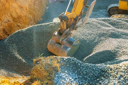 Excavators moving gravel in the construction works of a foundation in the house. Stockfoto