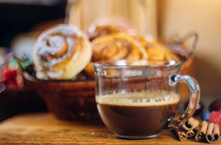 Cinnamon rolls with coffee on wooden table soft focus