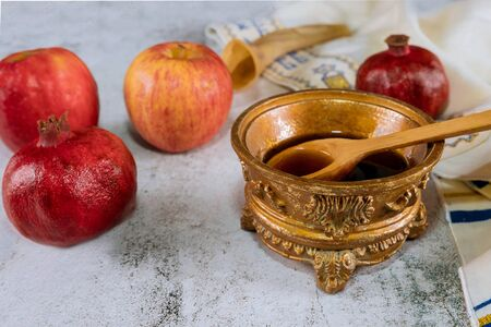 Rosh hashanah with glass honey jar and fresh ripe apples. Jewish new year symbols shofar and tallit Banco de Imagens