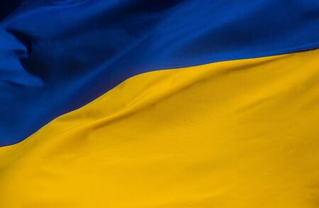 National yellow blue of closeup of the flag of the Ukraine Standard-Bild - 130813456